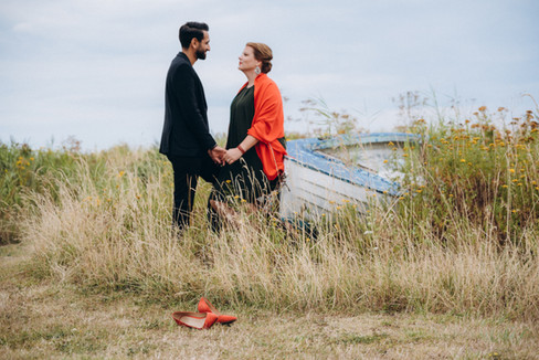Man and wife exploring the grasslands and nearby boats on coastal Lolland island during their vow renewal abroad experience, inspired by our Denmark wedding packages.
