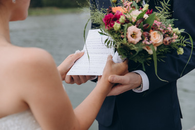 A groom putting a ring on his bride's finger during their lake wedding in Denmark.