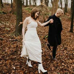A couple holding hands and walking through Mon Island forest during their wedding in Denmark