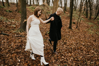 Newlyweds holding hands and exploring the forest in Mon Island during their winter elopement to Denmark as a part of their Scandinavian wedding abroad.