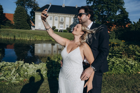 Newlyweds taking a selfie during their wedding abroad in Denmark, enjoying their adventure elopement at the Lolland-Falster islands.