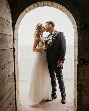 Newlyweds kissing under the arches of Old Hojerup Church, a top Denmark wedding venue on UNESCO World Heritage Site Stevens Klint.