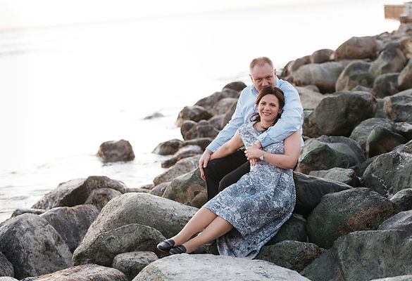 A couple sitting on the rocks by the seaside and embracing during their adventure escape to Denmark where they had their vow renewal abroad.