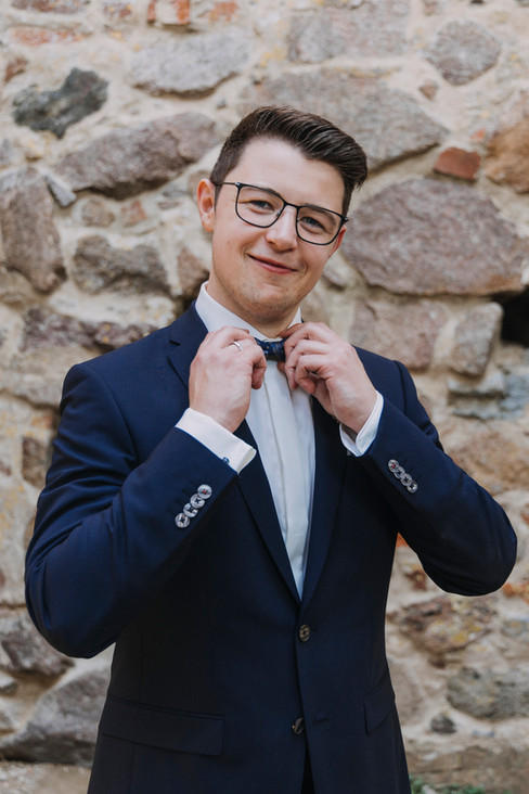A  groom smiling and straightening his bowtie during his adventure elopement on Bornholm Island.