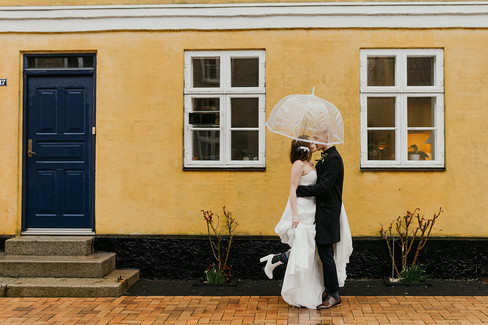 Newlyweds kissing under an umbrella during their Mon Island wedding, enjoying their adventure elopement in Denmark as they explore the picturesque towns.