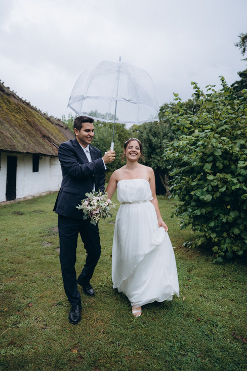 A groom holding up an umbrella for his smiling bride while they elope abroad with one of our elopement packages abroad, ideal for couples that want to experience the green nature and open-air museums of Denmark.