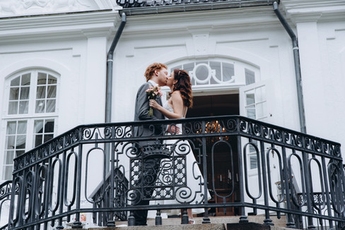 Newlyweds kissing in front of the beautiful Denmark wedding venue, the Vindeholme Castle, one of the best places to elope abroad for UK couples.