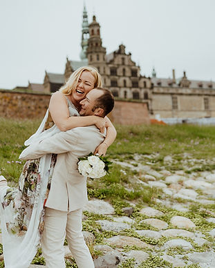 A groom hugging and lifting up his happy bride in front of Hamlet's Elsinore Castle during their small intimate wedding abroad in Denmark.