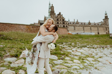 A groom lifting up his bride as they enjoy their Denmark wedding package at Hamlet's Elsinore Castle