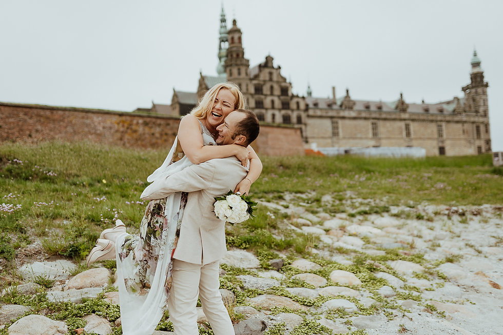 A couple embracing warmly in front of Kronborg Castle, during their small castle wedding in Denmark.