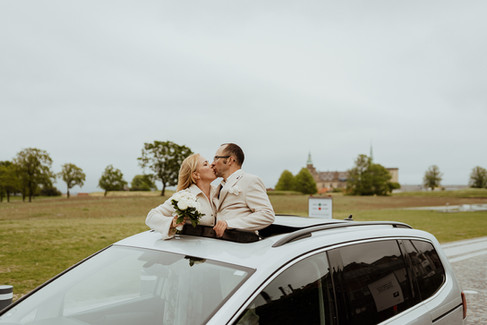 Newlyweds kissing outside of a car roof as they enjoy their adventure wedding in Denmark.