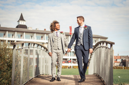 A couple holding hands and crossing a bridge while on their same-sex wedding in Denmark, one of the best place to get married abroad for gay couples.