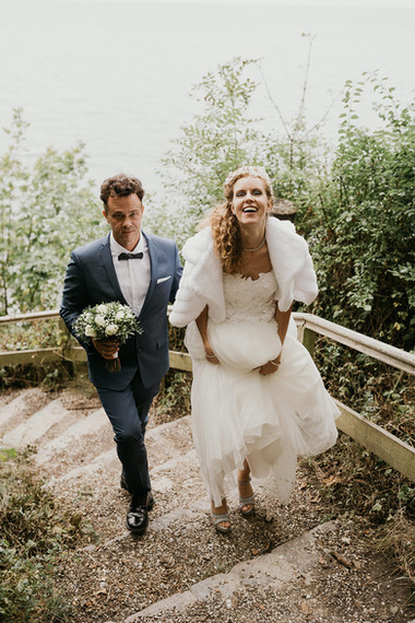 A groom and bride climbing up the natural path surrounding their dream Denmark wedding venue.