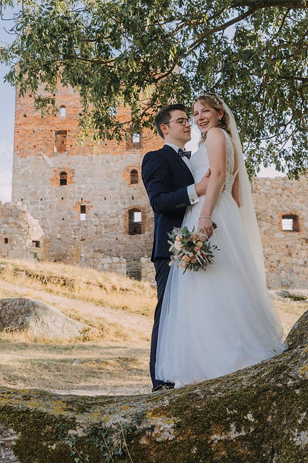 A couple posing near castle ruins at their adventure wedding abroad.
