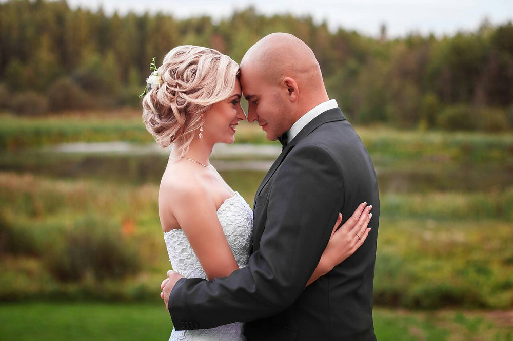 A bride and groom leaned their heads against each, after they had eco-style, environment friendly wedding on Danish islands