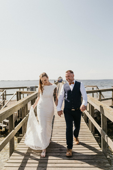 Newlyweds walking by the Hestehoved Jetty during their Nordic wedding in Lolland Island as they enjoy getting married in Denmark