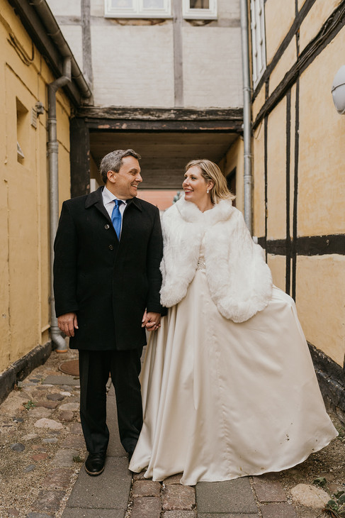Husband and wife holding hands and walking through Maribo on Lolland Island during their winter elopement to Denmark, a perfect marry abroad idea for travel lovers.