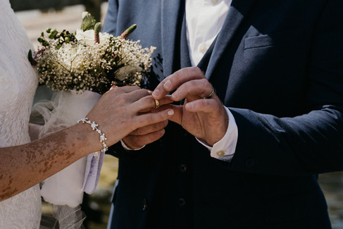 A groom putting a ring on his bride during their Nordic wedding ceremony after booking out Denmark elopement package