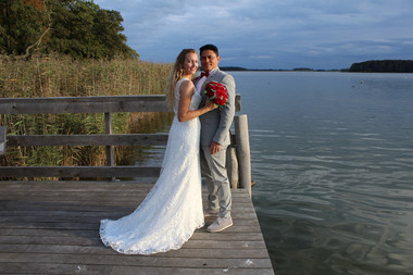 A romantic portrait of newlyweds by the Maribo Lake on Lolland Island as they enjoy their marriage in Denmark for foreign couples.