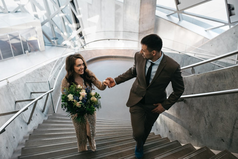 Elena and Andre holding hands and climbing up a staircase while renewing their wedding vows abroad in Denmark.