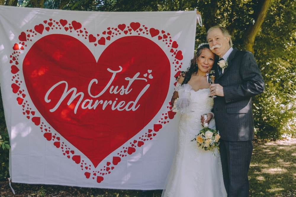 Just married senior couple posing into camera.