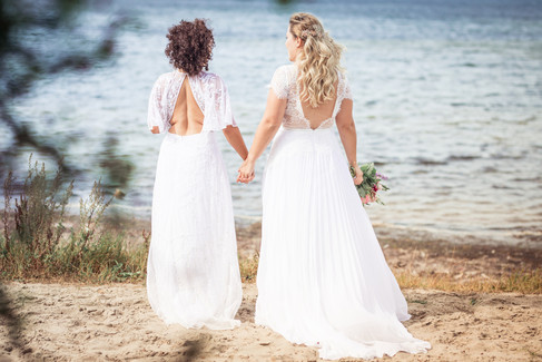 A lesbian couple holding hands and looking at the sea as they enjoy their gay marriage in Denmark, one of the best places for LGBT intimate weddings.