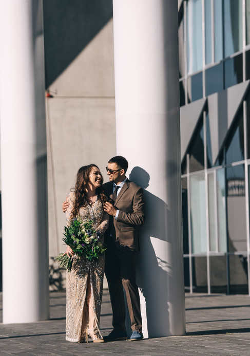 A husband hugging his wife in front of a modern urban building while they renew their vows abroad, ideal also for weddings in Denmark