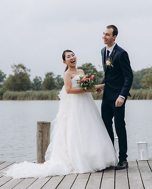 Husband and wife laughing at the Maribo Lakes in Lolland Island during their small wedding abroad in Denmark.