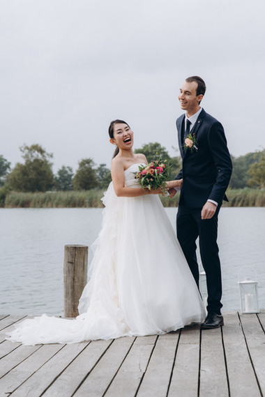 Newlyweds laughing during their Scandinavian lake wedding on Lolland Island in Maribo Town during their elopement in Denmark.