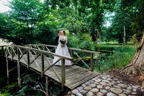 Newlyweds on a wooden bridge at a romantic park during their forest island wedding adventure in Denmark.