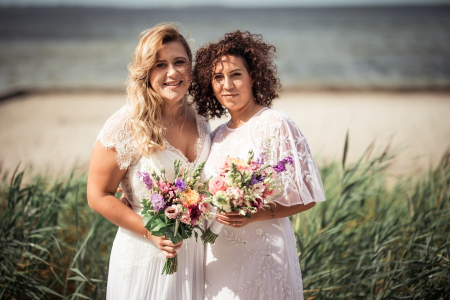 Lesbian couple getting married in Denmark and each bride holds nice summer wedding flowers