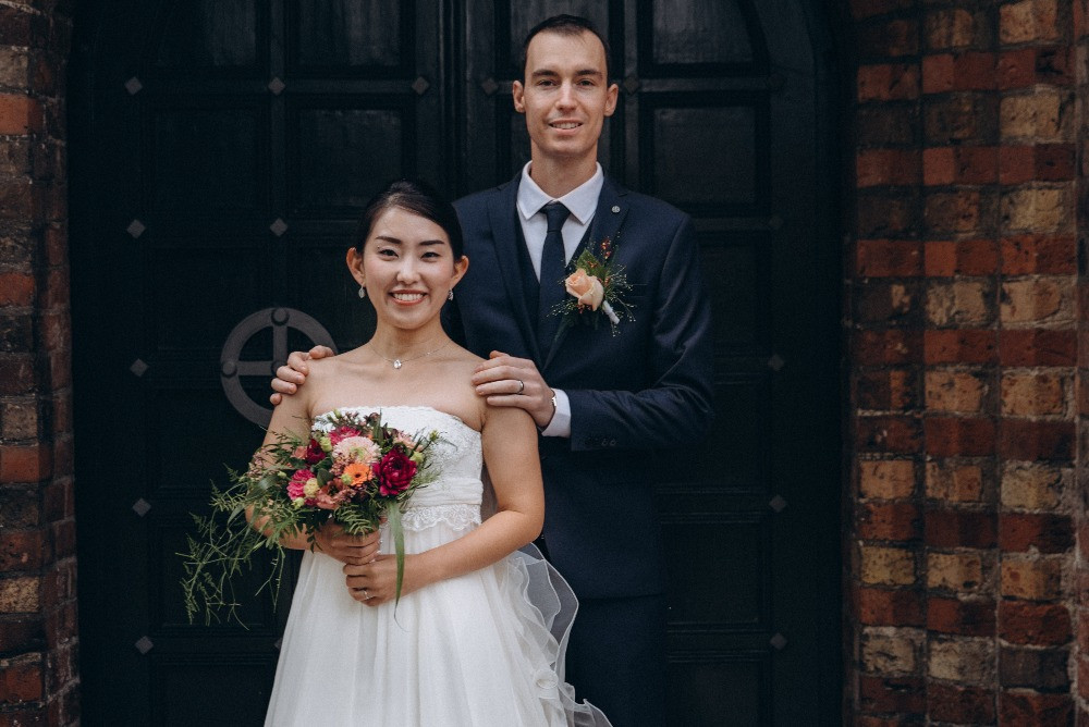 A portrait of newlyweds, where the bride holds her delicate wedding bouquet in pink and pastel colorsю