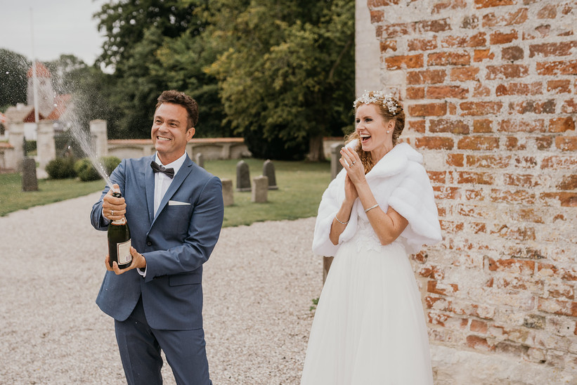 A couple popping champagne in front of the Old Hojerup Church, one of the best destination weddings in Denmark.