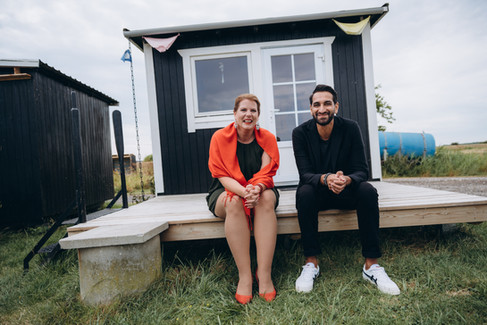 A couple sitting by a beach cottage and smiling after they renew wedding vows