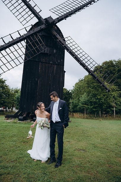 Nywlyweds laughing in the front of the old mill during their outdoor wedding in Denmark
