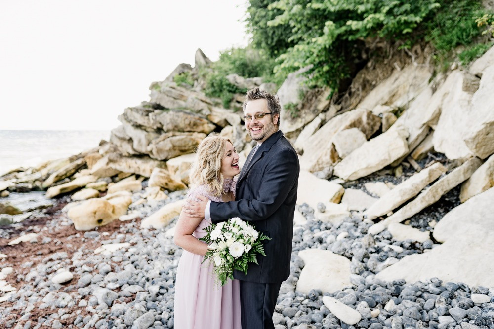 couple laughing by the sea while the bride is holding a white wedding bouquet