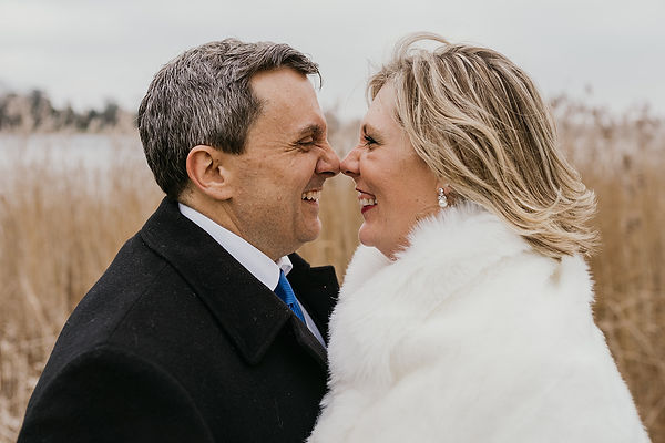 An American couple doing an Eskimo kiss during their small wedding abroad on the Danish Islands.