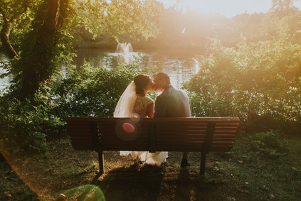 Newlyweds sitting on the bench and kissing.
