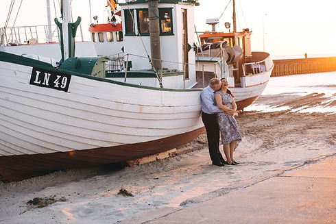 An elopement ceremony in Denmark is all about experiencing the hidden treasures, pictures a newlywed couple laughing by a boat.