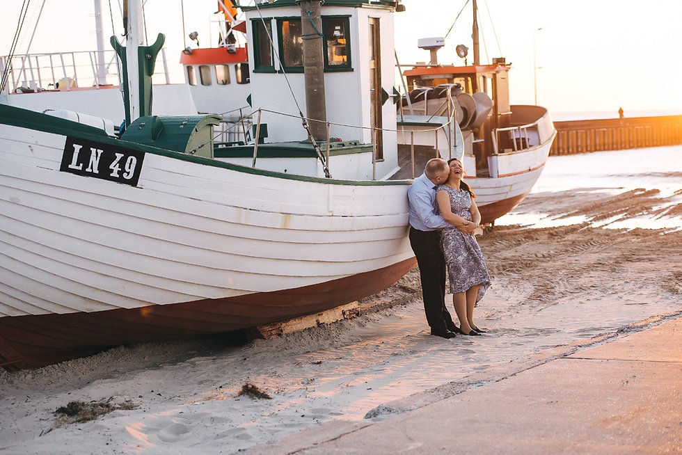 The kissing couple on the beach by the sheep after their wedding vows renewal abroad in Denmark.