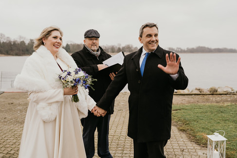 Newlyweds holding hands as the groom waves to the camera enjoying their adventure wedding at Lolland Island, one of the best places to elope abroad.