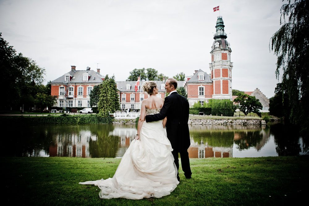 Newlyweds in the front of the Danish castle as they get married in the castle