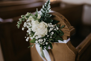 A charming detail of a flower arrangement tied on a church wedding chair, one of the many beautiful preparations that go into our Denmark wedding packages.