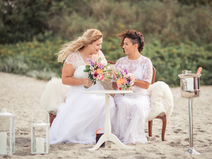 Newlyweds sitting at their organized Nordic beach wedding, the location they chose for their lesbian wedding.