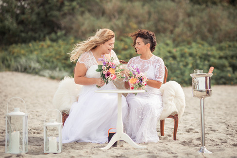 A lesbian couple sitting at the beach signing their wedding papers as they enjoy their same-sex wedding abroad in Denmark.