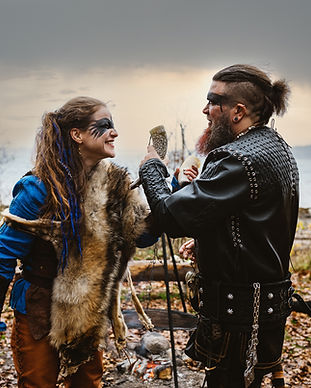 A couple locking arms during their Viking-themed wedding at the Land of Legends historic museum.