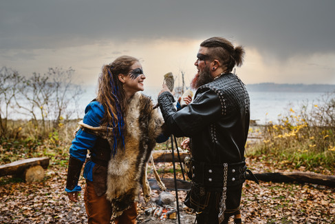 A husband and wife performing a Nordic wedding, traditional and historical, by the sea and fire.