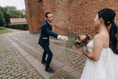 A groom reaching towards his bride as they are getting married in Denmark at the Great Cathedral in Maribo.