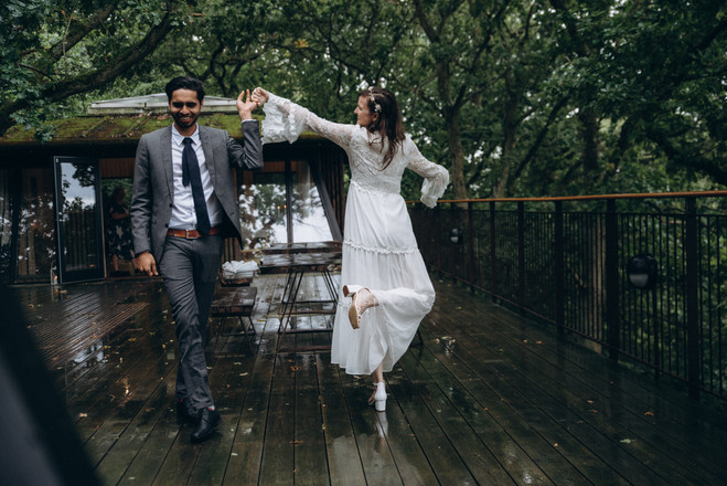 A couple dancing in the train with umbrellas at a Nordic treehouse, enjoying their elopement package for two during their island wedding experience.
