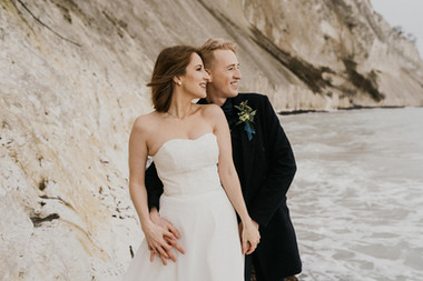 Newlyweds hugging and smiling as they look out into the distance during their winter wedding in Denmark